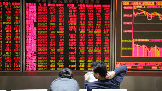 Investors observe the stock market at an exchange hall in Beijing, China.
