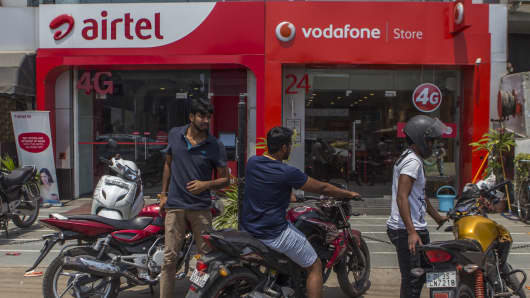 Motorcyclists park their bikes outside Bharti Airtel and Vodafone India stores in New Delhi, India.