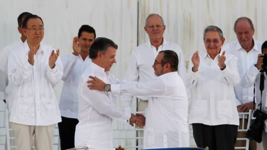 Colombian President Juan Manuel Santos (L) and Marxist rebel leader Timochenko shake hands after signing an accord ending a half-century war that killed a quarter of a million people, in Cartagena, Colombia.