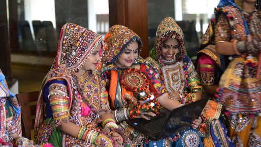 Indian folk dancers from the Panghat Group of Performing Arts use a laptop during a dress rehearsal for an event to mark the forthcoming Hindu festival 'Navaratri', or the Festival of Nine Nights, in Ahmedabad on September 25, 2016.