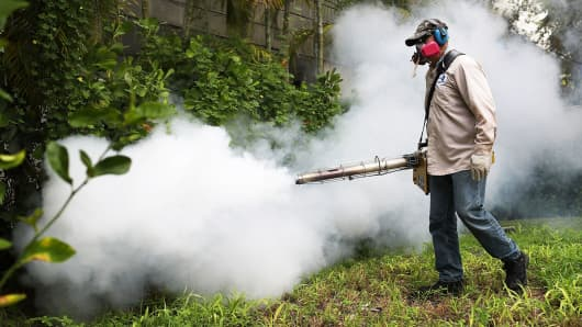 A Miami-Dade County mosquito control inspector sprays pesticide in a Miami Beach neighborhood as the county fights to control the Zika virus outbreak on August 24, 2016.