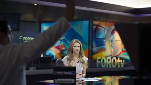 A producer gives a signal to Ana Paula Ordorica, an anchor for Grupo Televisa SAB's FOROtv news channel, at the Televisa studios in Mexico City, Mexico.