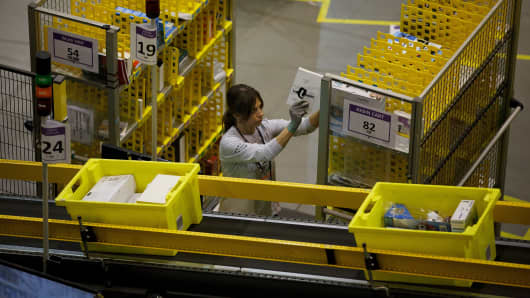 An employee arrange items for distribution at the Amazon fulfillment center in Spain.