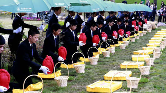 Chinese funeral workers prepare urns for burial at the Shimenfeng memorial park during a ceremony in conjunction with the Qingming festival in Wuhan, China's Hubei province.