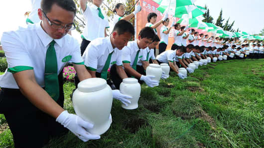 Attendants place biodegradable urns in their r