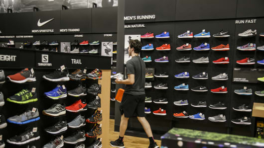 An employee carries Nike Inc. sneakers for a customer at a Dick's Sporting Goods Inc. store in Sterling Heights, Michigan