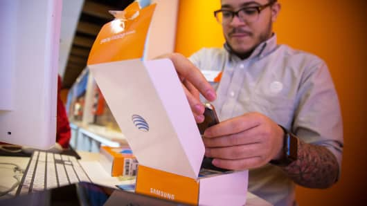 An AT&T employee assists a customer with a Samsung smartphone inside one of the company's stores in New York.