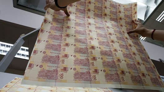An employee inspects sheets of Mexican hundred pesos notes at the Banco de Mexico printing factory in Mexico City, Mexico.