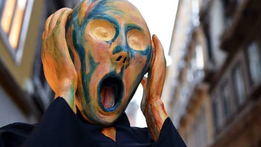 A costumed reveller wearing a mask depicting Munch's famous painting 'The Scream'