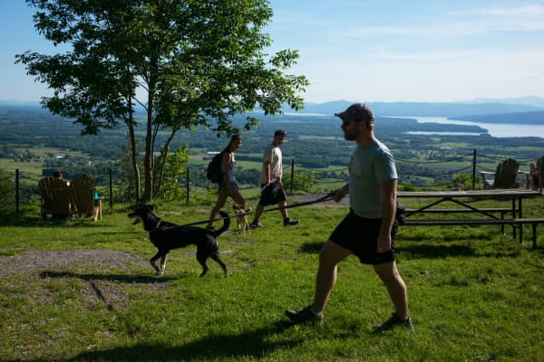 A view of hikers, several with pet dogs, at a scenic overlook site in Mount Philo State Park, Charlotte, Vermont.