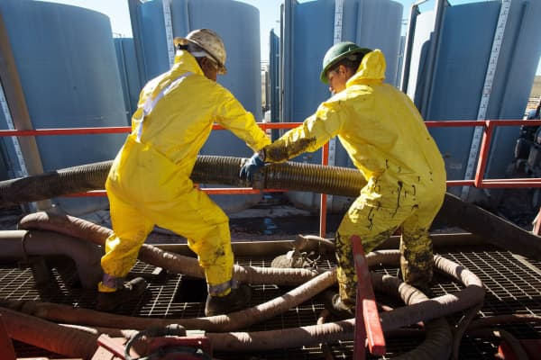 Workers connecting tubes on the Raven Oil Drilling rig near Watford City N.D.