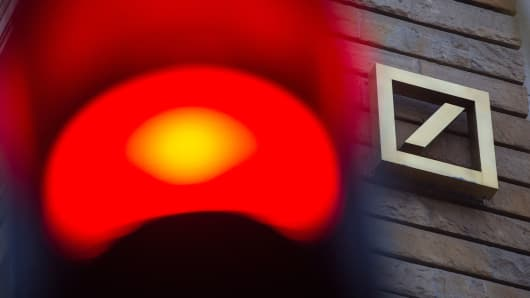 A red traffic light stands illuminated as the logo of Deutsche Bank AG sits on the exterior of the bank's offices in Berlin, Germany.