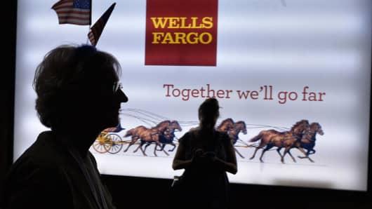 A woman passes a Wells Fargo sign.