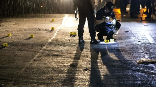 Scene of the Crime Operatives (SOCO) work at the scene where two suspects were shot dead following an encouter and shootout with police at a checkpoint along a highway in Manila on August 28, 2016.
