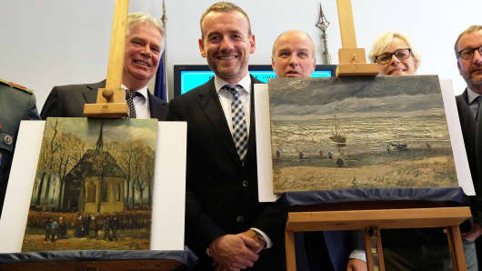 Axel Ruger, Director of the Van Gogh museum poses next to Congregation Leaving the Reformed Church in Nuenen' (L) and 'The Beach At Scheveningen During A Storm' (R) by Vincent van Gogh, two Van Gogh paintings stolen in Amsterdam 14 years ago and recently recovered by organized crime investigators in Italy, on September 30, 2016.