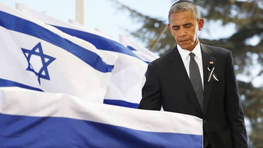 President Barack Obama touches the coffin of Shimon Peres after delivering his eulogy during the funeral at Mount Herzl Cemetery on September 30, 2016 in Jerusalem, Israel.