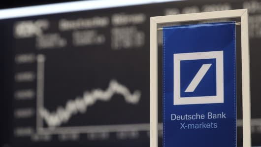 A banners of Deutsche Bank is pictured in front of the German share price index, DAX board, at the stock exchange in Frankfurt, Germany, September 30, 2016.