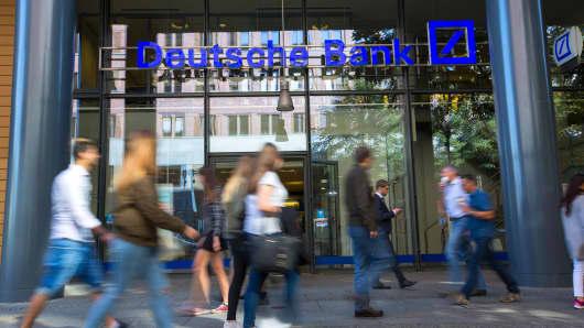 Pedestrians walks past a Deutsche Bank AG bank branch in Berlin, Germany, on Tuesday, Sept. 27, 2016.