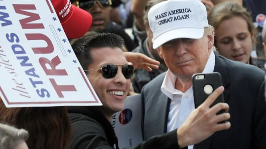A supporter of Donald Trump takes a selfie with the Republican presidential candidate at a rally in front of the USS Wisconsin on October 31, 2015 in Norfolk, Virginia.