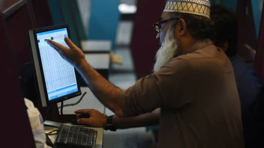 Pakistani stock brokers watch the latest share prices during a trading session at the Pakistan Stock Exchange in Karachi on September 29.