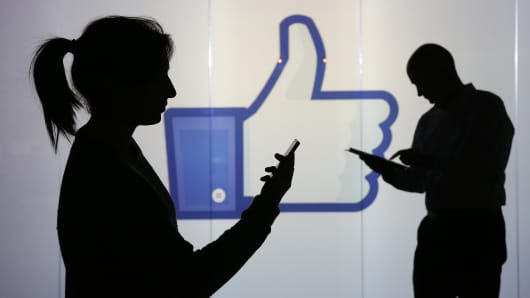 People stand and work on mobile devices, a smartphone, left, and a Apple Inc. iPad whilst framed against a wall bearing Facebook Inc.s 'Thumbs Up' symbol