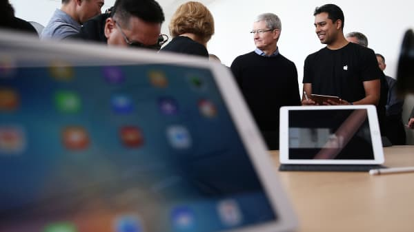 Apple CEO Tim Cook looks at a display of the new 9.7' iPad Pro during an Apple special event at the Apple headquarters on March 21, 2016 in Cupertino, California.