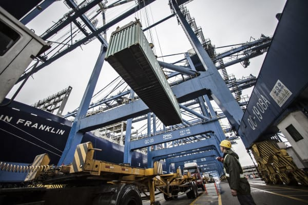 A dock worker directs the loading of shipping containers onto CMA CGM SA's Benjamin Franklin container ship docked at the Guangzhou Nansha Container Port in Guangzhou, China.
