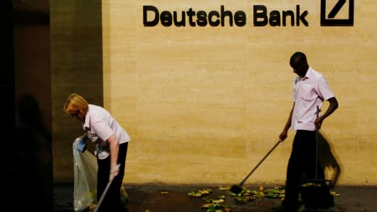 Workers sweep leaves outside Deutsche Bank offices.