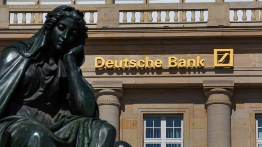 A signs stands above the entrance to a Deutsche Bank AG bank branch in Frankfurt, Germany, on Monday, July 4, 2016.