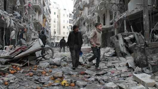 An elderly Syrian man and a child walk amidst debris in a residential block reportedly hit by an explosives-filled barrel dropped by a government forces helicopter.