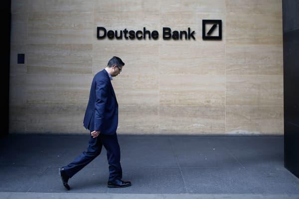 A pedestrian passes a Deutsche Bank logo outside the offices of Deutsche Bank AG in London.