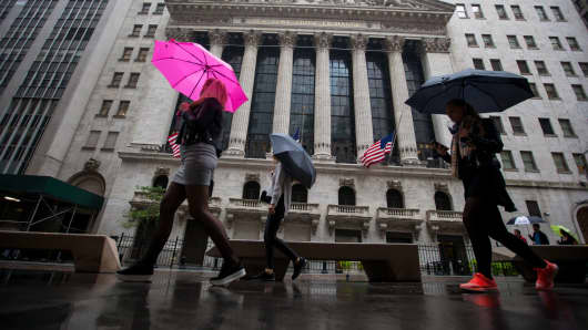 Pedestrians holding umbrellas pass outside the New York Stock Exchange.