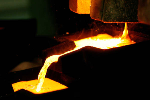 Mixed gold and silver are poured into ingot molds at the furnace facility.