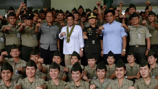 Philippine President Rodrigo Duterte (C) with Defense Secretary Delfin Lorenzana (centre L) and Army chief Eduardo Ano (centre R) during a 'talk to the troops' visit to meet military personnel in Manila on October 4, 2016. Duterte launched a fresh tirade at the United States on October 4, telling Obama to 'go to hell' as the longtime allies launched war games that the firebrand leader warned could be their last.