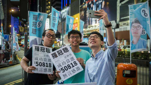 Nathan Law (R) and Joshua Wong (C) at a rally in Causeway bay following Law's win in the Legislative Council election in Hong Kong on September 5, 2016. A new generation of young Hong Kong politicians advocating a break from Beijing looked set to become lawmakers for the first time on September 5 in the biggest poll since mass pro-democracy rallies in 2014.