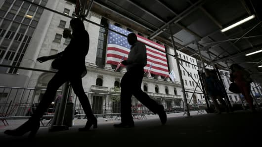 Morning commuters pass in front of the exterior of the New York Stock Exchange (NYSE) in New York.