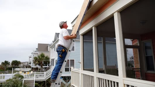Brent Scurry of Lake City, South Carolina climbs a ladder to install window shutters at an ocean front home in anticipation of Hurricane Matthew in Garden City Beach, South Carolina, U.S. October 5, 2016.