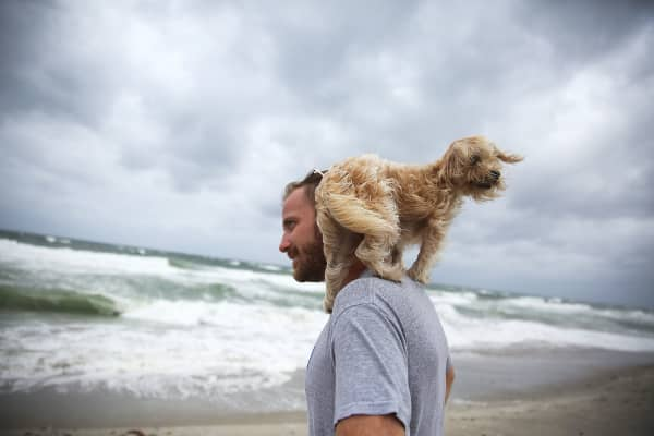 Ted Houston and his dog Kermit visit the beach as Hurricane Matthew approaches the area on October 6, 2016 in Palm Beach, United States. The hurricane is expected to make landfall sometime this evening or early in the morning as a category 4 storm.