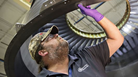 An employee inspects damaged area of a composite engine case during repair at the GE Aviation manufacturing facility in Batesville, Mississippi.