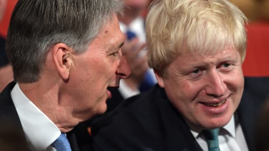 Foreign Secretary Boris Johnson (R) and Chancellor of the Exchequer Philip Hammond chat before Prime Minister Theresa May delivers a speech during the fourth day of the Conservative Party Conference.