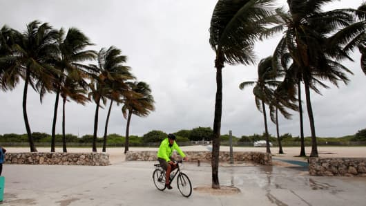 A man rides his bicycle along the beach prior to the arrival of Hurricane Matthew in Miami Beach, Fla, Oct. 6, 2016.