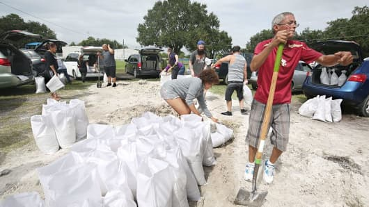 Locals scramble to fill sandbags with the last of a supply at the Road and Bridge Department in Kissimmee, Florida, in preparation for the landfall of Hurricane Matthew.