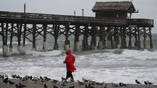 A man walks near the Cocoa Beach Pier as Hurricane Matthew approaches, October 6, 2016 on Cocoa Beach, Florida.