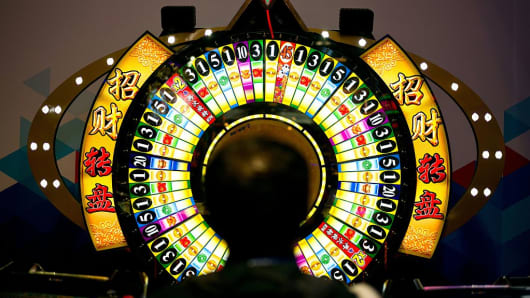 A man tries his luck at a wheel of fortune machine at the Global Gaming Expo Asia held in Macau on May 17, 2016.
