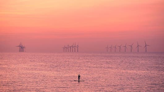A paddleboarder is pictured on the water near Leasowe at Liverpool Bay in the Irish Sea at sunset on August 15, 2016.