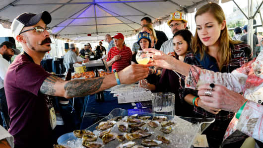 People serve beer with oysters at the Great Annual Beer Festival in Denver.