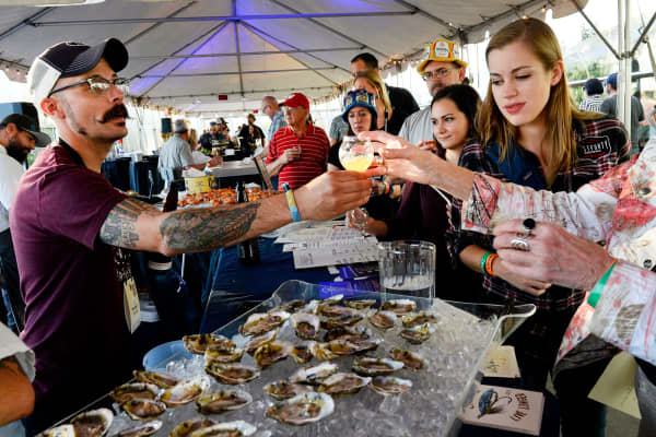 People serve beer with oysters at the Great American Beer Festival in Denver.