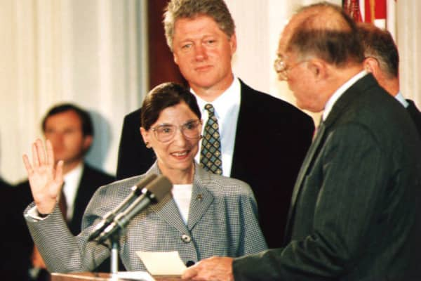 Chief Justice of the U.S. Supreme Court William Rehnquist (R) administers the oath of office to newly-appointed U.S. Supreme Court Justice Ruth Bader Ginsburg (L) as President Bill Clinton looks on 10 August 1993.