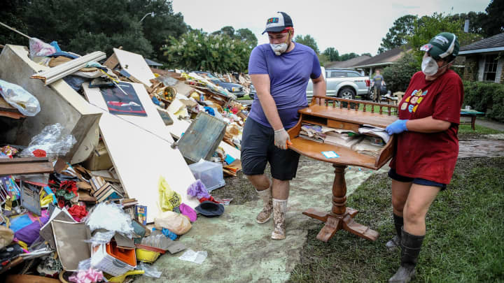 Residents throw furniture damaged in floods in Baton Rouge, Louisiana, Aug. 22, 2016.