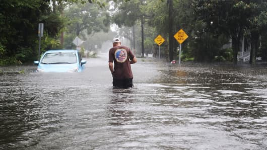 A man walks through a flooded street as Hurricane Matthew passes through the area on October 7, 2016 in St Augustine, Florida.